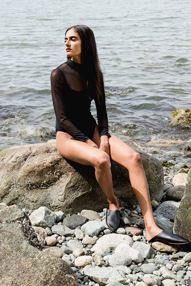 Model wearing long-sleeved Bond swimsuit by Canadian swimwear designer Beth Richards